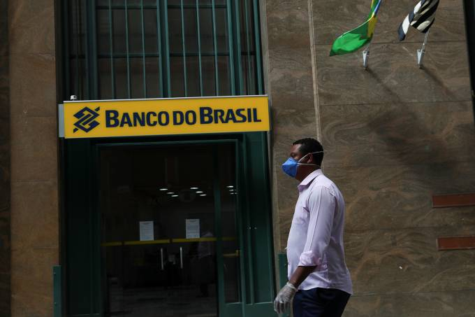 -coronavírus-A man wearing a protective face mask and gloves walks in front of Banco do Brasil (Bank of Brazil) during the coronavirus disease (COVID-19) outbreak in Sao Paulo