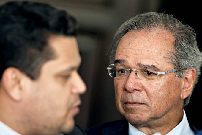 Brazil's Economy Minister Paulo Guedes looks on near Brazil's President of the Senate Davi Alcolumbre as he speaks to the media outside his home in Brasilia