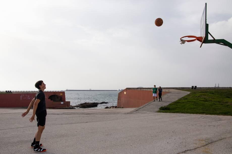 Criança joga basquete na praia de Matosinhos, em Portugal. Por lá, esportes ao ar livre estão liberados, mas apenas de forma individual