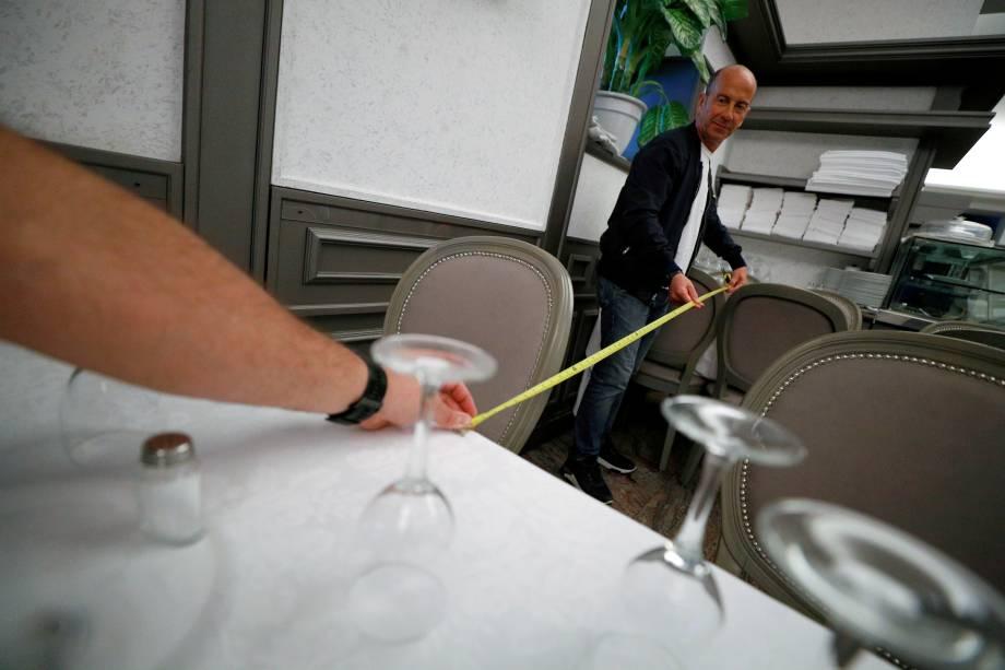 Proprietários do restaurante Nuova Fiorentina, em Roma, medem a distância entre as mesas para garantir a manutenção do distanciamento social entre os clientes.
