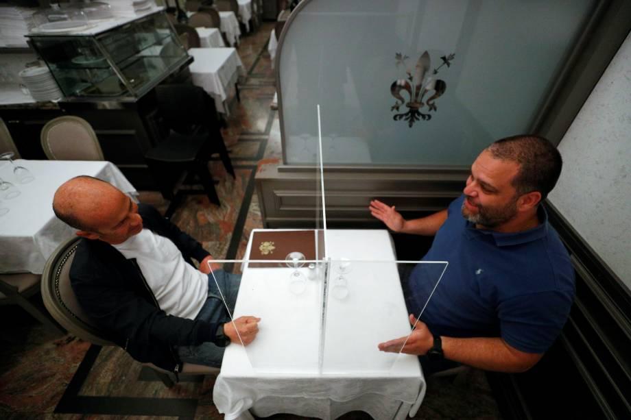 Alberto Iannelli e Fabio Andreotti, proprietários do restaurante Nuova Fiorentina, em Roma, na Itália,testam a tela protetora instalada em uma mesa do restaurante.