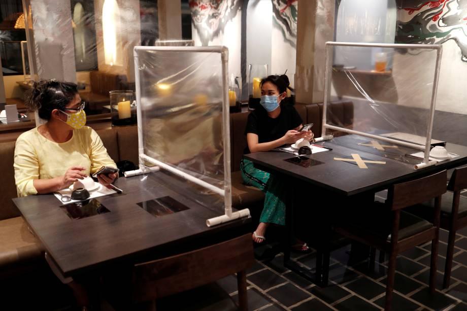 Outro restaurante em Bangkok, na Tailândia. adotou a barreira plástica entre as mesas.