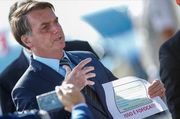 """Brazil's President Jair Bolsonaro holds a paper with a print of the WhatsApp message with former minister Sergio Moro, written below in Portuguese: """"This is gossip"""" as he leaves Alvorada Palace, amid the coronavirus disease (COVID-19) outbreak in Brasilia"""