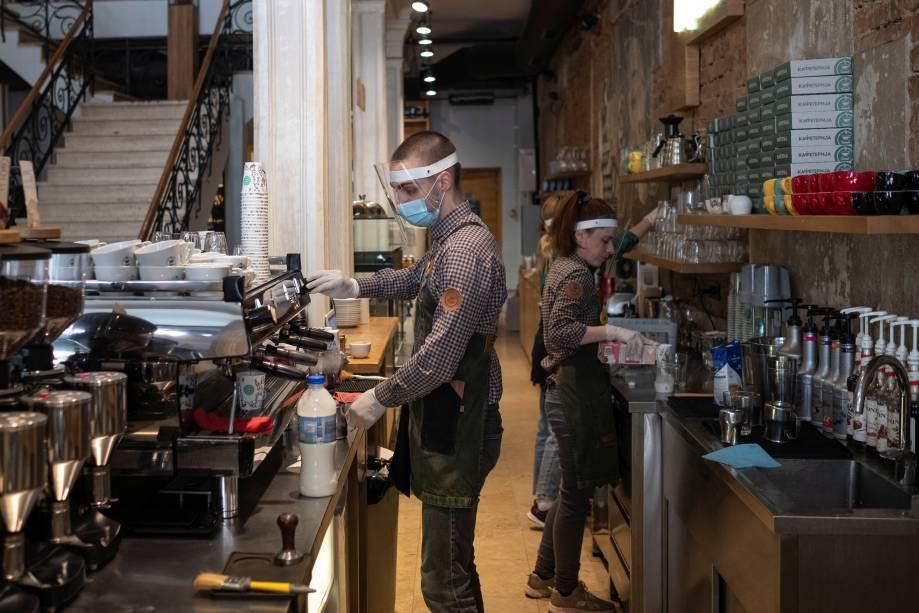 Barista usa uma máscara protetora enquanto prepara um cappuccino dentro de um café em Belgrado, na Sérvia.