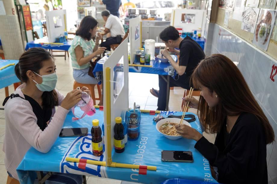 Barreira plástica permite que clientes compartilhem a mesma mesa em um restaurante Bangkok, na Tailândia, após o relaxamento das restrições.