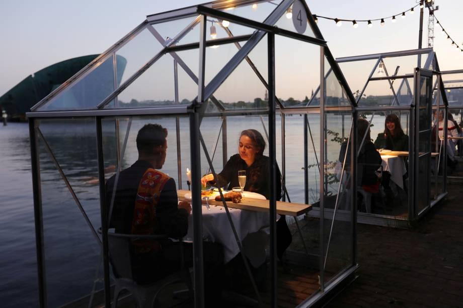 Restaurante em Amsterdã, na Holanda, implementa o uso de estufas individuais para manter a distância segura entre os clientes e evitar a propagação do novo coronavírus.