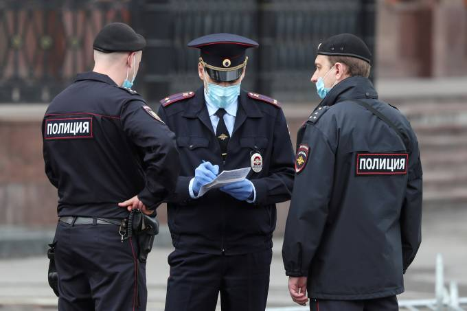 FILE PHOTO: Police officers wearing protective face masks speak in a street amid the outbreak of the coronavirus disease in Moscow