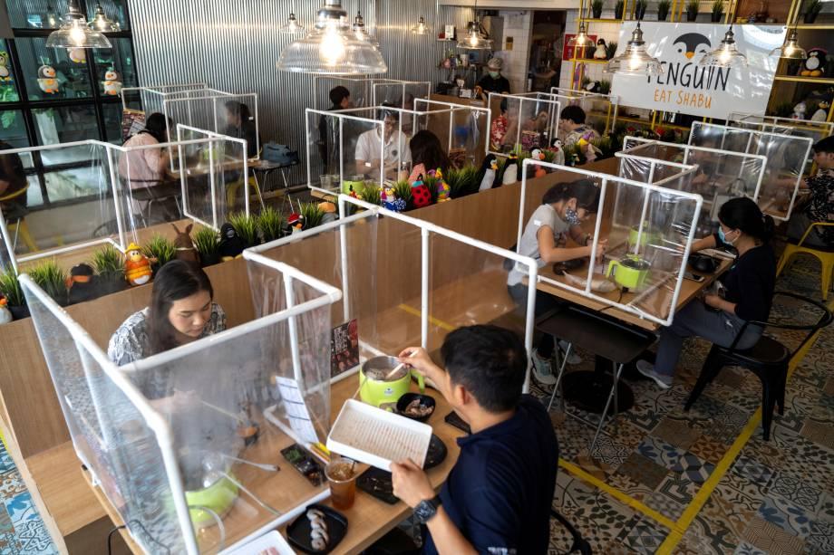 Restaurante em Bangkok, na Tailândia, usa uma barreira plástica para manter as medidas de distanciamento social entre os clientes.