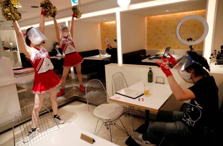 Garçonetes usam máscaras protetoras, escudos e luvas enquanto fazem sus performance no restaurante temático 'Cheers One' em Tóquio, no Japão.