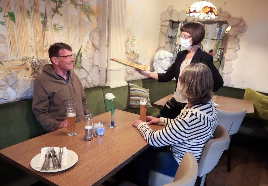 Garçom usa máscara para servir os clientes no restaurante Tuscolo, em Bonn, na Alemanha.