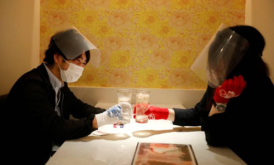 Clientes de um restaurante em Tóquio, no Jaão, usam máscaras,protetores faciais e luvas para prevenir infecções após o surto da Covid-19.