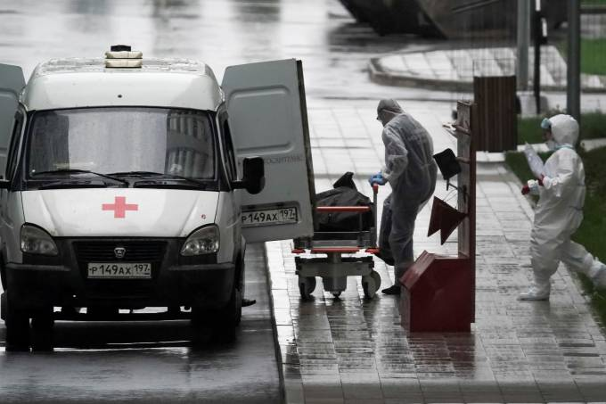A medical specialist wearing protective gear push a stretcher outside a hospital for patients infected with the coronavirus disease on the outskirts of Moscow
