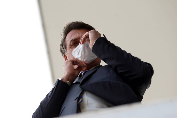 Brazil's President Jair Bolsonaro adjusts his protective mask as he speaks with journalists, amid the coronavirus disease (COVID-19) outbreak, at the Planalto Palace, in Brasilia