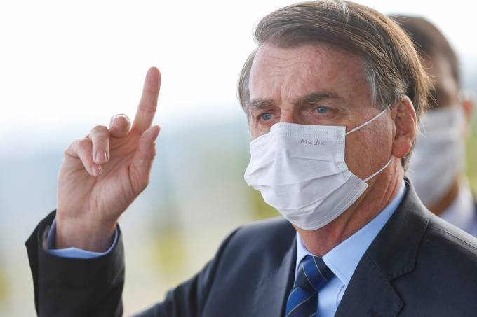 Brazil's President Jair Bolsonaro wearing a protective face mask reacts as he leaves Alvorada Palace, amid the coronavirus disease (COVID-19) outbreak in Brasilia