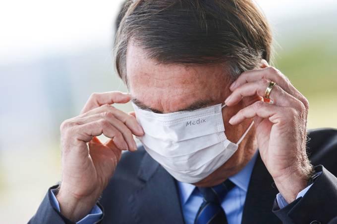 Brazil's President Jair Bolsonaro adjusts his mask as he leaves Alvorada Palace, amid the coronavirus disease (COVID-19) outbreak in Brasilia