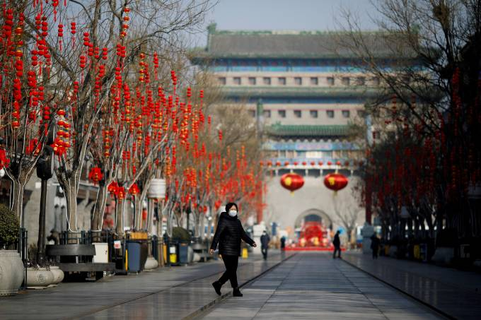 FILE PHOTO: Woman wearing a face mask walks on the Qianmen pedestrian street in the morning after the extended Lunar New Year holiday caused by the novel coronavirus outbreak, in Beijing