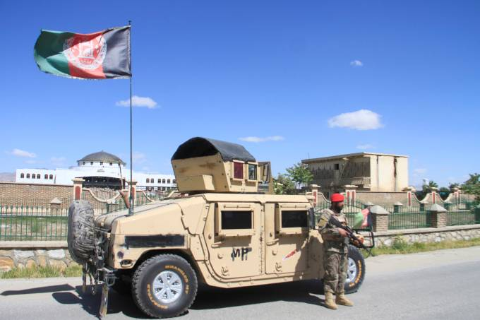 An Afghan Natiolan Army officer stands guard at the site of a blast in Ghazni province, Afghanistan
