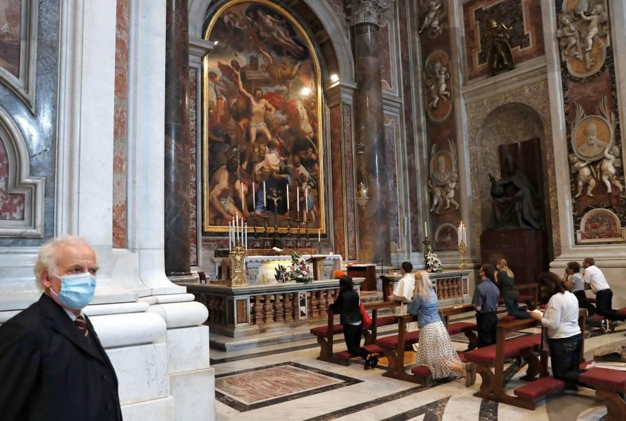 Fiéis rezam na Basílica de São Pedro, no Vaticano, no primeiro dia após a reabertura da catedral e relaxamento das medidas de isolamento social na Itália - 18/05/2020