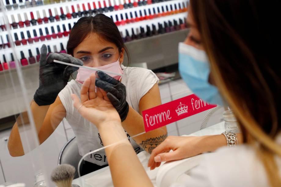 Manicure faz as unhas de cliente através de vidro protetor em Roma, Itália - 18/05/2020