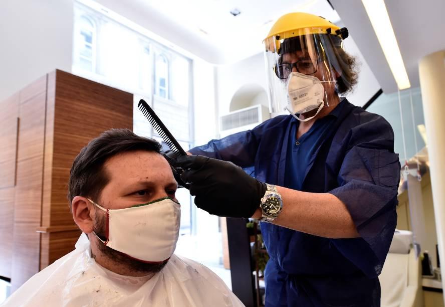 Cabeleireiro usa escudo protetor durante atendimento em salão de beleza em Milão, na Itália - 18/05/2020