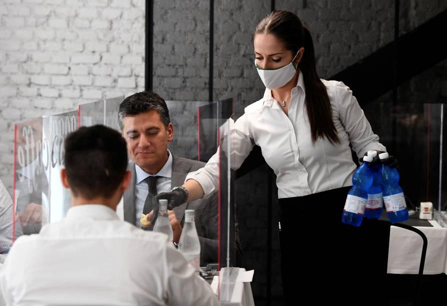 Garçonete serve clientes em Milão no primeiro dia de reabertura de restaurantes, bares e cafés na Itália - 18/05/2020