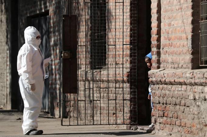 Mulher com roupa de proteção conversa com criança imigrante em Santiago, no Chile