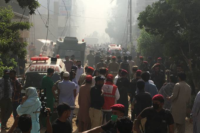 Ambulances and fire brigade vehicles gather at the site of a passenger plane crash in a residential area near an airport in Karachi