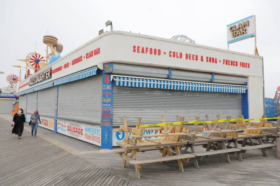Memorial Day: Coney Island beach, em Nova York - 22/5/2020People walk by a closed restaurant on the boardwalk at Coney Island beach ahead of the Memorial Day weekend following the outbreak of the coronavirus disease (COVID-19) in Brooklyn, New York City, U.S., May 22, 2020.