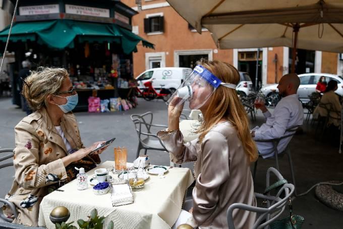 Mulher toma café em Roma com máscara de proteção – 18.5.20