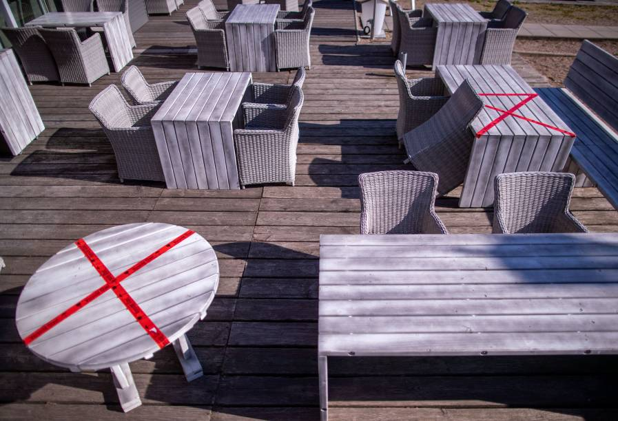 Um restaurante ao ar livre no lago Schwerin, na Alemanha, usou fita vermelha para isolar alguns assentos e garantir que seja mantida a distância mínima entre os clientes.