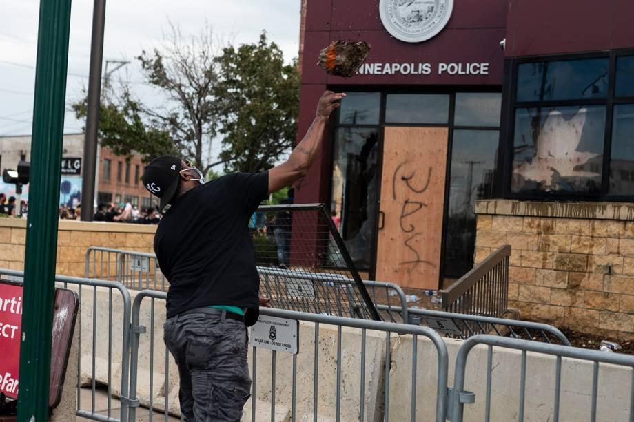 Um manifestante arremessa um pedaço de concreto no prédio da Delegacia de Polícia em Minneapolis, Minnesota