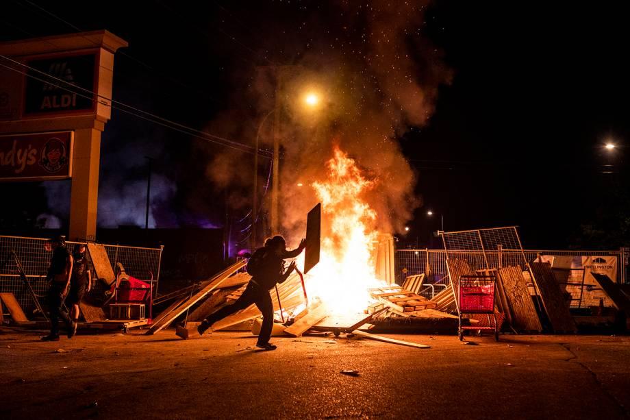 Um manifestante lança um pedaço de madeira em um incêndio na rua ao norte da 3ª Delegacia de Polícia em Minneapolis, Minnesota