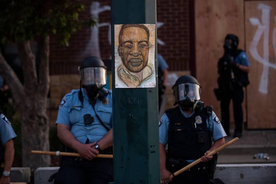 Um retrato de George Floyd pendurado em um poste de luz de rua enquanto policiais vigiam a 3ª Delegacia em Minneapolis, Minnesota