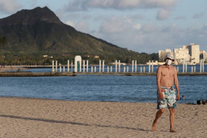 FILE PHOTO: A beachgoer wearing a protective mask walks down Waikiki Beach, with Diamond Head mountain in the background