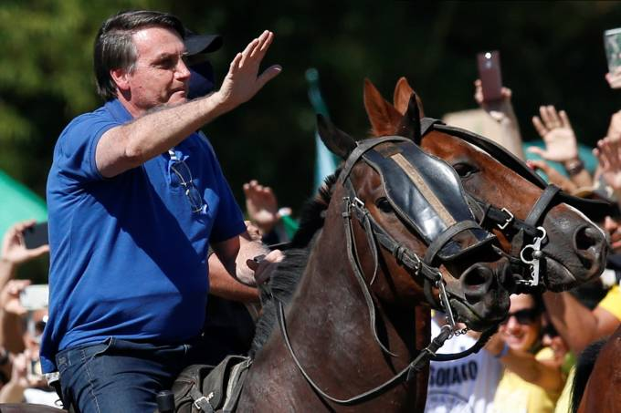 Brazil's President Jair Bolsonaro rides a horse during a meeting with supporters protesting in his favor, amid the coronavirus disease (COVID-19) outbreak, in Brasilia