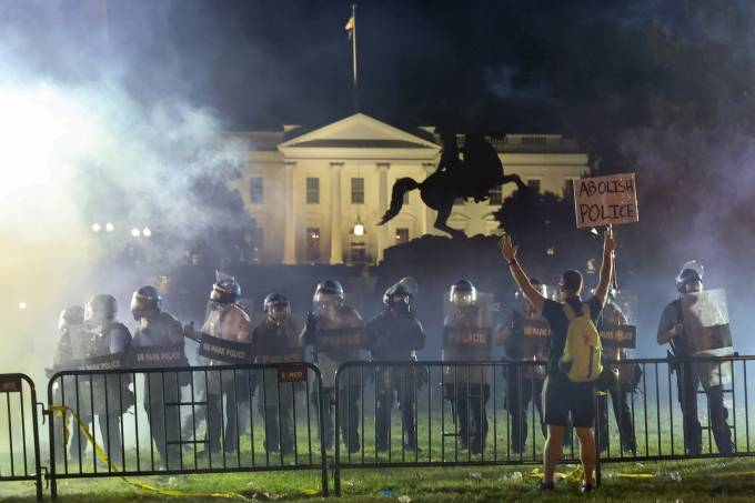 Police in riot gear keep protesters at bay in Lafayette Park near the White House in Washington