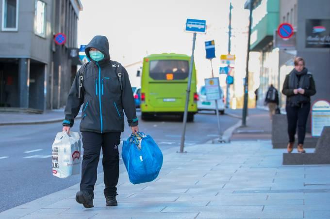 Homem com máscara de proteção carrega sacola de compras em rua de Oslo
