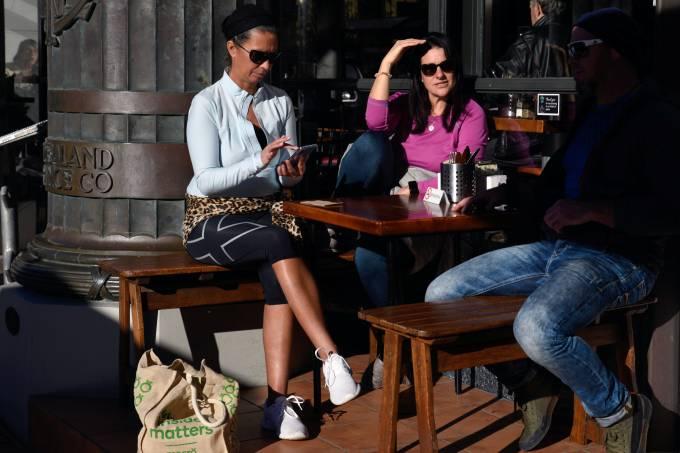 Clientes de café na Nova Zelândia conversam na área externa após suspensão total de restrições