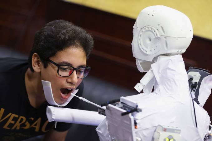 The remote-controlled robot that has been built by the Egyptian mechanical engineer Mahmoud El komy, 26, tests a boy for the coronavirus by running PCR tests, limiting exposure to suspected cases, in Cairo