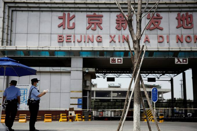 Police officers wearing face masks stand guard outside an entrance to the Xinfadi wholesale market in Beijing
