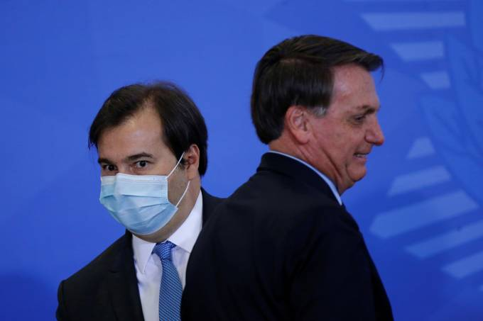 President of Brazil's Lower House Rodrigo Maia is seen next to Brazil's President Jair Bolsonaro during an inauguration ceremony of the new Communications Minister Fabio Faria (not pictured) at the Planalto Palace, in Brasilia
