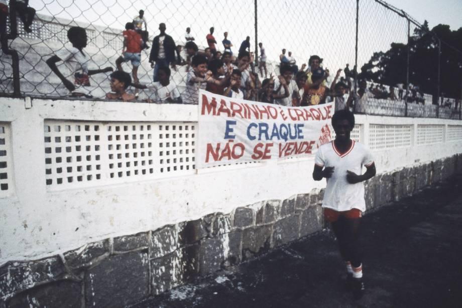 """Marinho passando em frente a uma faixa com os dizeres """"Marinho é craque e craque não se vende"""", em 1985"""