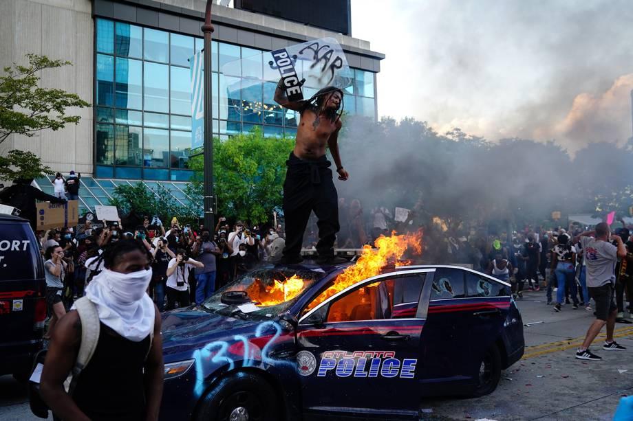 Um manifestante sobe em cima de um carro da polícia em chamas durante um protesto em Atlanta, Geórgia - 29/05/2020