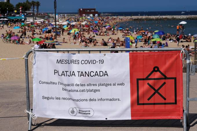 "A banner reads ""Beach Closed"" as people enjoy the sunny weather, as Spain officially reopens the borders amid the coronavirus disease (COVID-19) outbreak, in Barcelona"