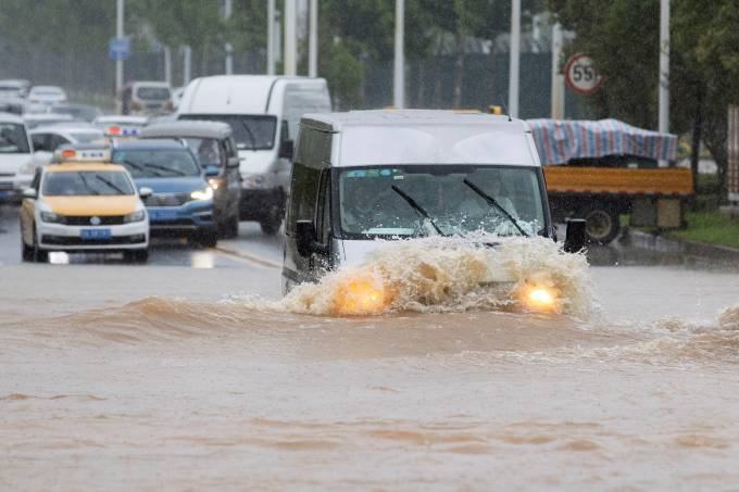 Vehicle travels through a flooded section of a road following heavy rainfall in Wuhan