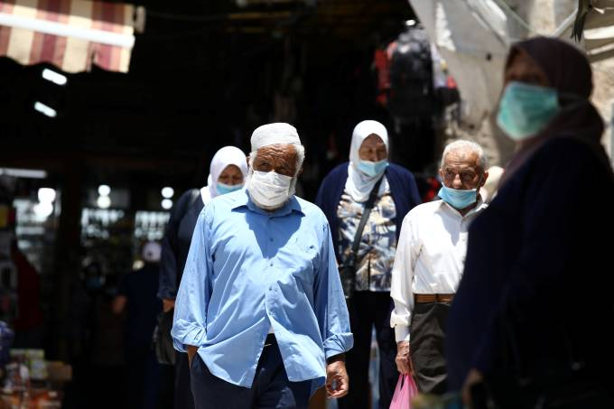 People wearing face masks to help fight the spread of the coronavirus disease (COVID-19) walk past shops in a market in Jerusalem's Old City