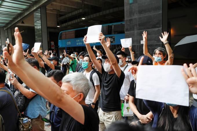 Manifestantes erguem cartazes em branco durante protesto em apoio a pessoas presas por protestar em Hong Kong