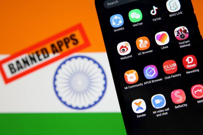 "FILE PHOTO: Smartphone with Chinese applications is seen in front of a displayed Indian flag and a ""Banned app"" sign"