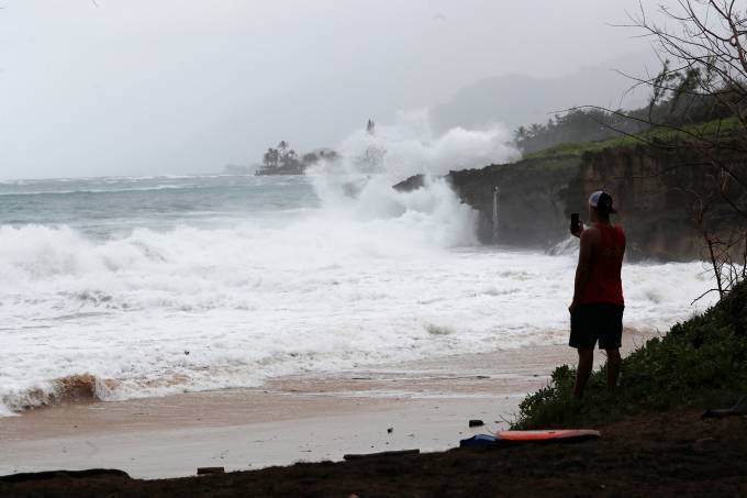 A beach goer watches the big waves wash up on Pounder's Beach in Laie, Hawaii, U.S. July 26, 2020, as Hurricane Douglas makes its way towards Oahu