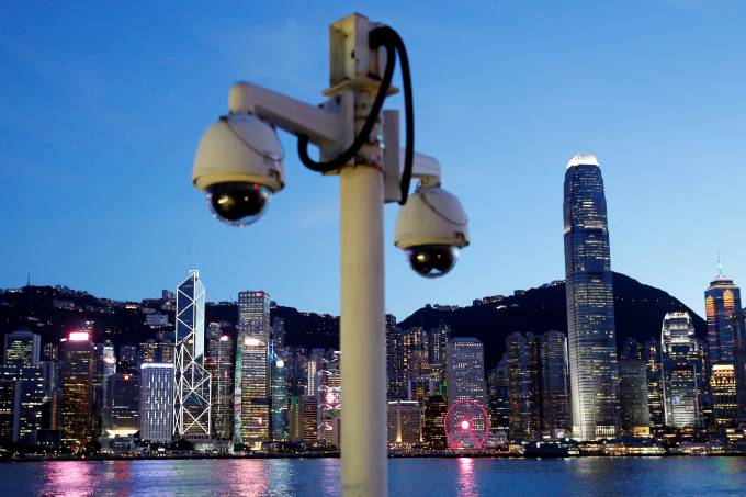 Pair of surveillance cameras are seen along the Tsim Sha Tsui waterfront as skyline buildings stand across Victoria Harbor in Hong Kong